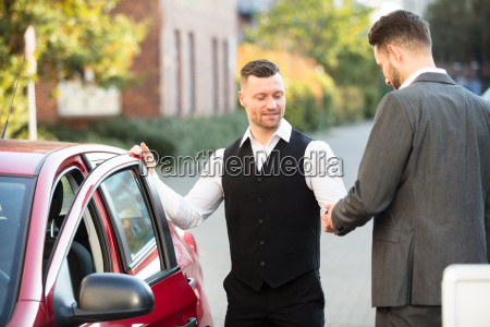smiling valet and businessperson standing near