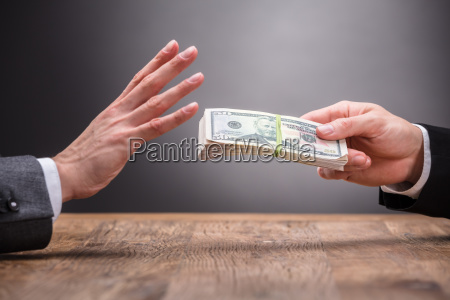 businessperson refusing to take bribe from