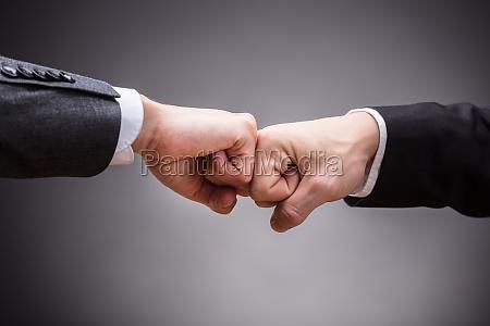 zwei wirtschaftler die faust stoss machen