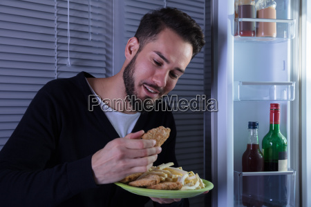 young man eating fried food