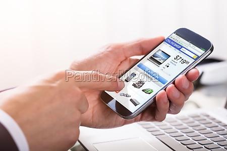 geschaeftsmann der online auf smartphone kauft