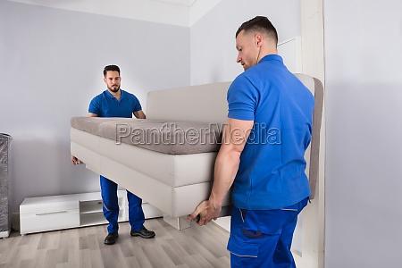 zwei maenner die sofa im wohnzimmer