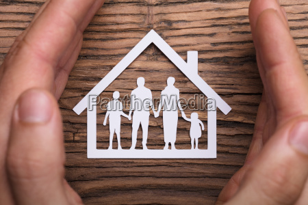 person holding protective hand on family