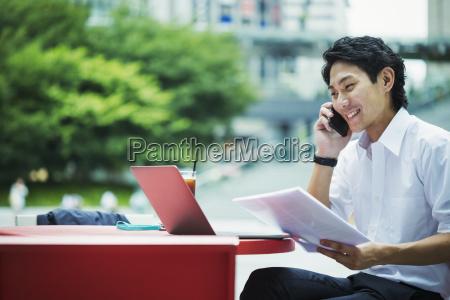 businessman wearing white shirt sitting outdoors