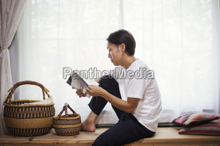 man sitting indoors on a wooden
