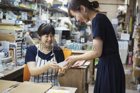 two smiling women sitting and standing