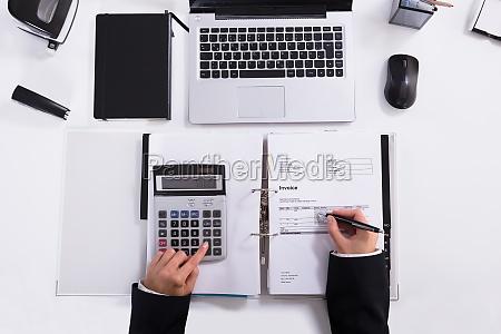 businesswoman hand calculating invoice using calculator