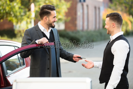 young businessman giving car key to