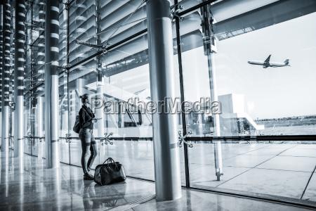 young woman waiting at airport looking