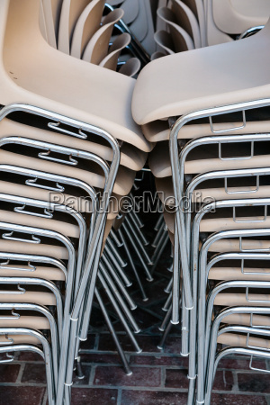 many stacked plastic chairs in outdoor