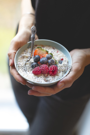 bowl with cereals porridge in hands