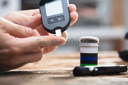 person checking blood sugar level with