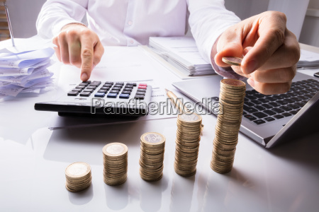 business person counting coins using calculator
