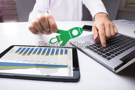 businessman holding green paper rocket and