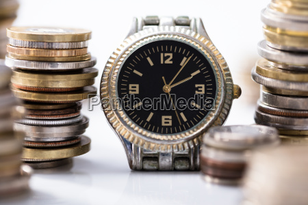 stack of coins with wrist watch