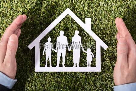person holding family home on grass