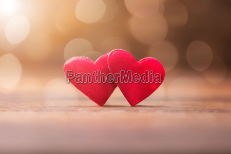 two red heart on wooden desk