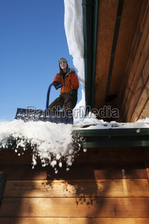 a young woman removes snow from