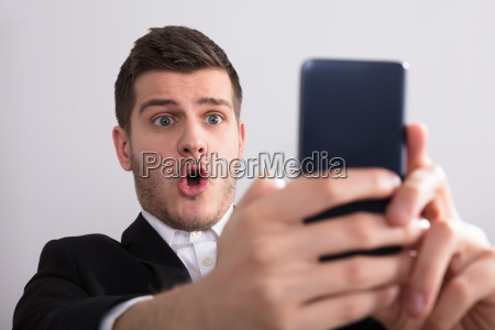 happy businessman looking at smartphone