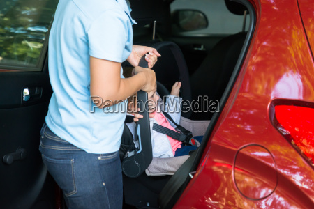 mother carrying baby on car seat