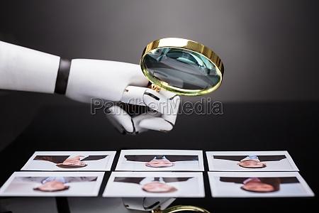 roboter der kandidatenphotographie mit lupe betrachtet