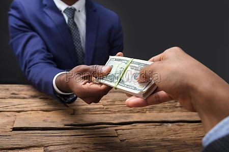 businessperson taking bribe from partner