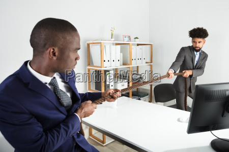 two young businessmen playing tug of