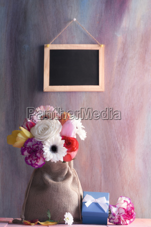 flower bouquet with gifts and blackboard