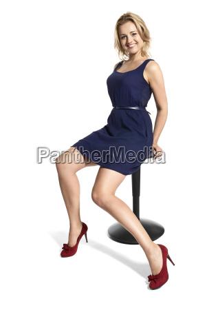 smiling blonde woman sitting on stool