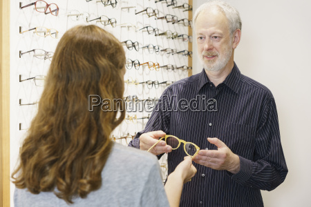 mature owner showing eyeglasses to woman