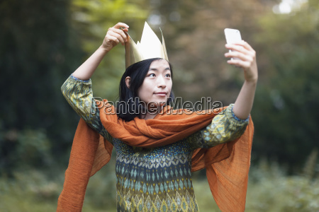 young woman wearing crown taking selfie
