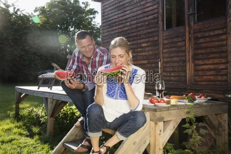 happy mature couple enjoying watermelon slice