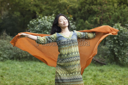 young woman holding orange scarf while