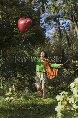happy young woman holding red heart