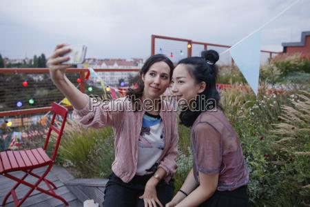 smiling women taking selfie with smart