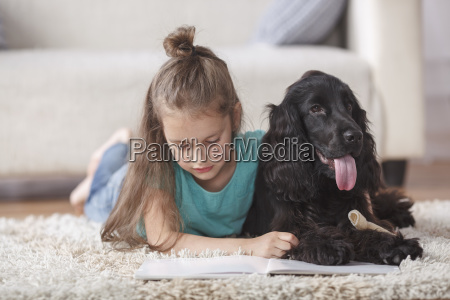 cute girl reading book while lying