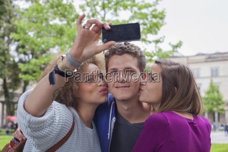 woman taking selfie with female friend