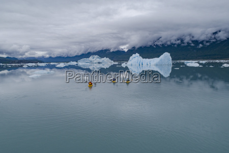 people canoeing in glacier lagoon against