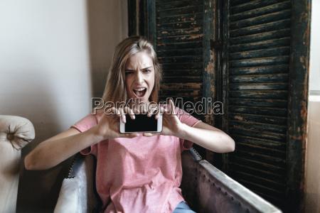 schreiende junge frau die smartphone selfie