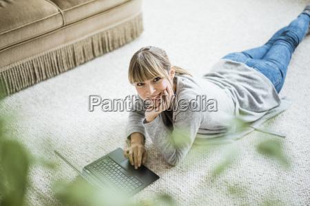laechelnde frau liegt mit laptop auf