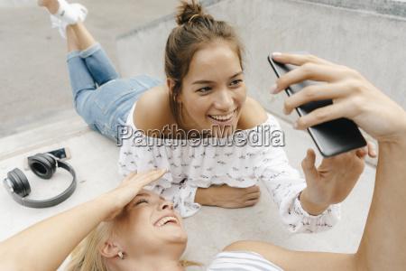 zwei froehliche junge frauen teilen sich
