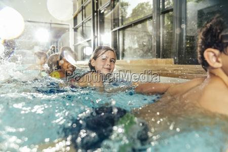 kinder im schwimmunterricht ueben am pool