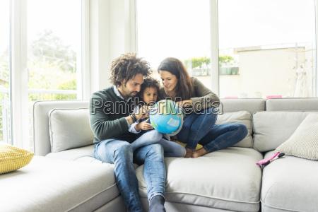 glueckliche familie sitzt auf der couch