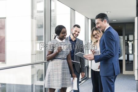 smiling business people with tablet talking