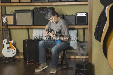 mature male musician playing guitar sitting