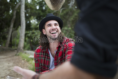 cheerful man looking at male friend