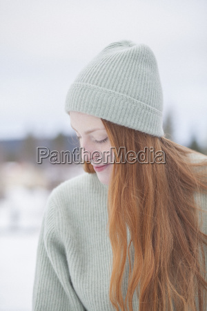 thoughtful young woman with long red