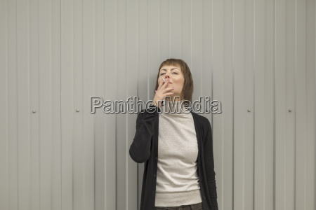 mid adult woman smoking cigarette while