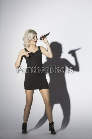 mid adult woman singing with microphone