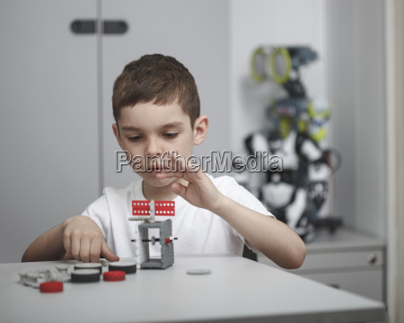 cute boy operating machinery at table